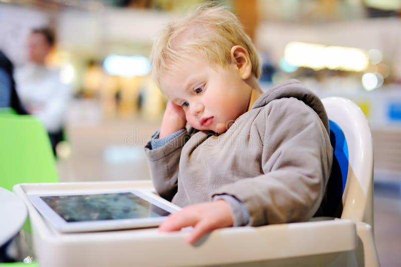 Uttråkat litet barn med en digital minnestavla arkivfoto