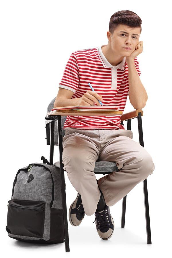 Uttråkat tonårs- studentsammanträde i en stol royaltyfri bild