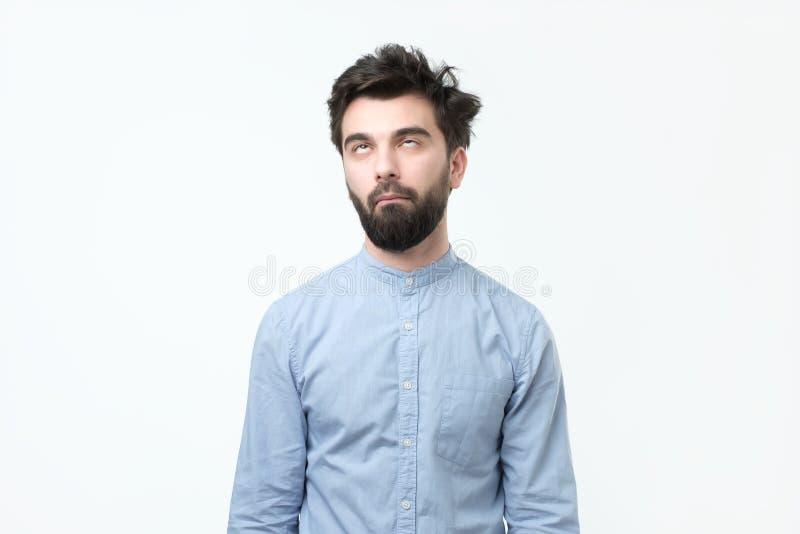 Uttröttad latinamerikansk man i den blåa skjortan som rullar upp hans ögon arkivbild