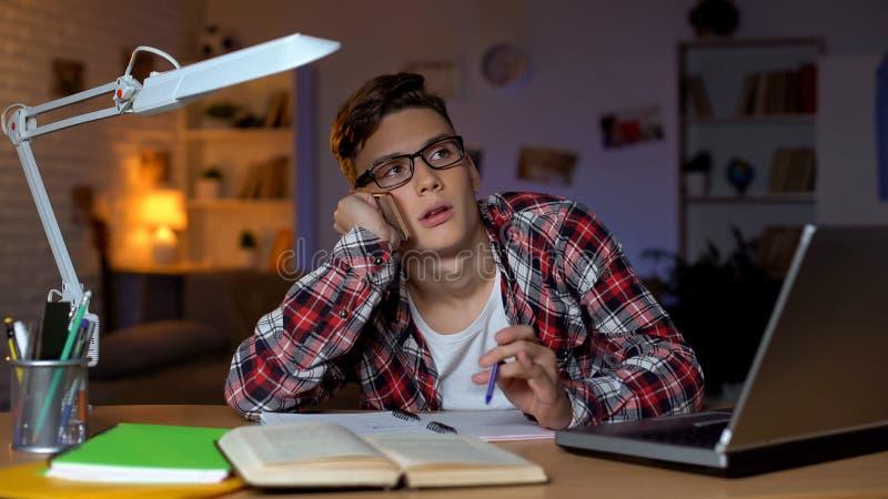 Uttr?kad student som pratar p? telefonen med v?nnen, i st?llet f?r att studera som sl?ser bort tid arkivfoto