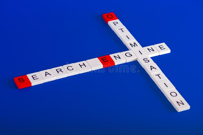 Uttryck för sökandemotorOptimisation SEO av trävita kvarter, blå bakgrund royaltyfria bilder