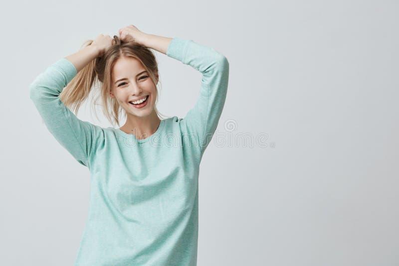Uttryck och sinnesrörelser för mänsklig framsida Den positiva unga härliga kvinnlign med färgat blont rakt hår i hästsvans klädde royaltyfri bild