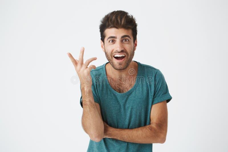 Uttryck, sinnesrörelser och känslor för mänsklig framsida Förvånad och förvånad skäggig ung man i blå t-skjorta som pekar på arkivfoto