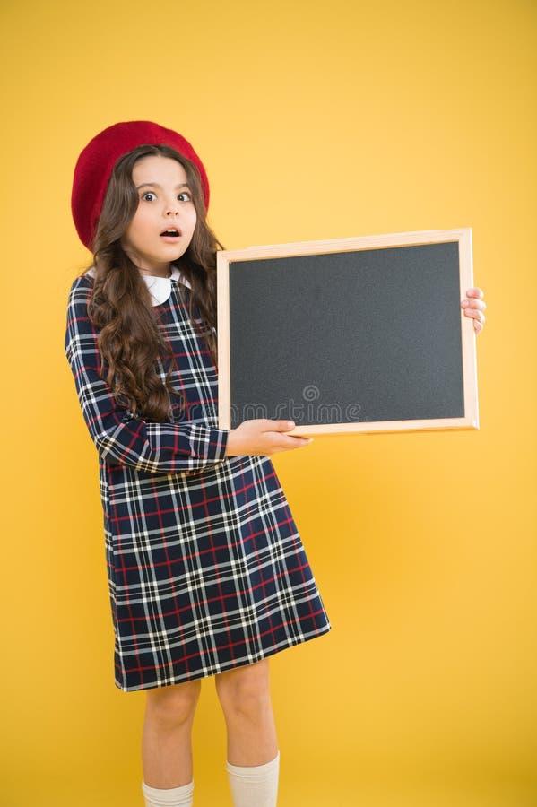 Uttrycka överraskning, skolashoppingförsäljningar Barn p? gul bakgrund annonsering av brädet för befordran Lycklig flicka in royaltyfria foton