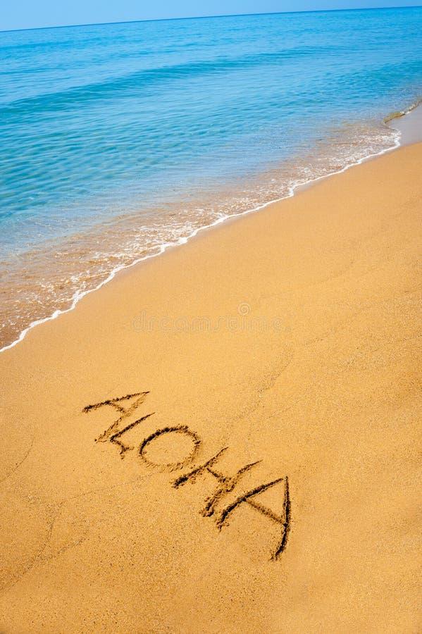 Uttrycka Aloha skriftligt i sandigt på den tropiska stranden royaltyfria bilder