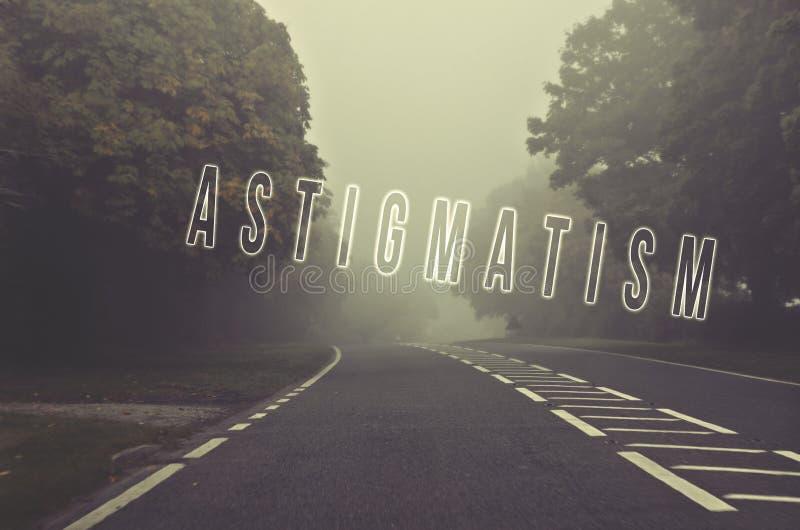 Uttrycka astigmatism som är skriftlig på faravägen på en dimmig dag Väg thr arkivfoto