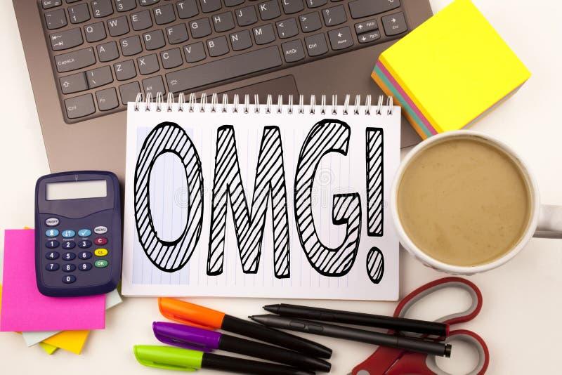 Uttrycka att skriva OMG oj min gud i kontoret med bärbara datorn, markören, pennan, brevpapper, kaffe Affärsidéen för överrasknin fotografering för bildbyråer