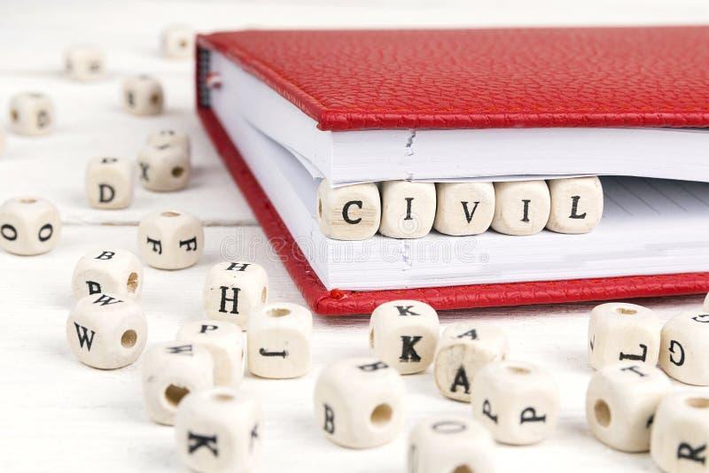 Uttrycka borgerligt skriftligt i träkvarter i anteckningsbok på vitt trä arkivfoton