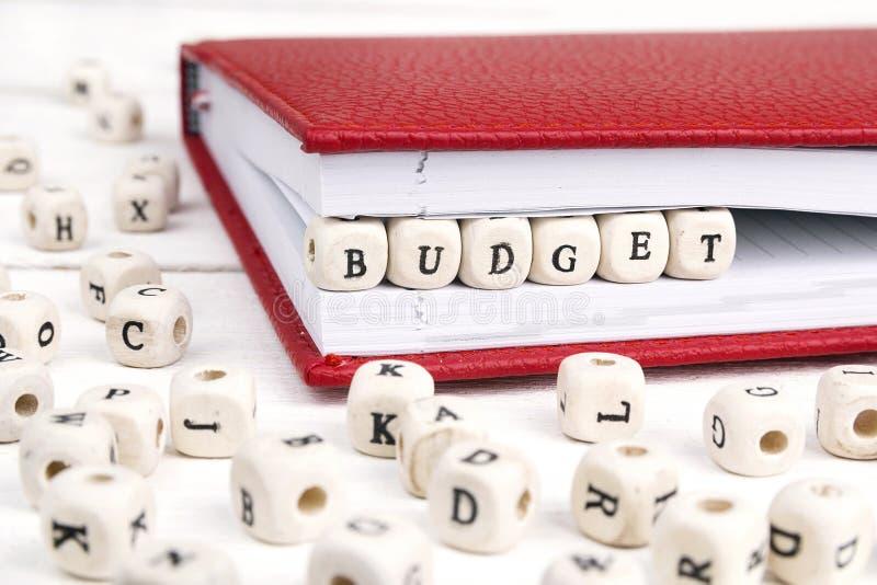 Uttrycka budget- skriftligt i träkvarter i röd anteckningsbok på vit wo royaltyfri bild