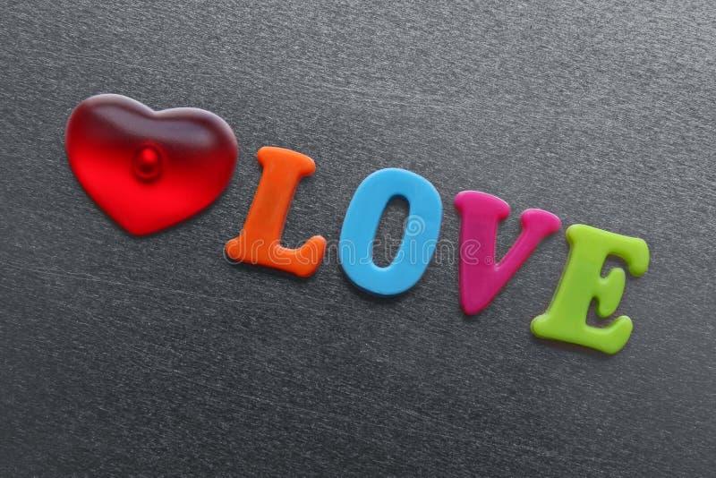 Uttrycka förälskelse med stavad röd hjärta ut genom att använda kulöra kylmagneter arkivbild
