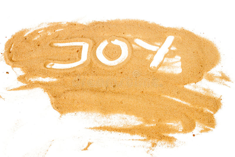 Uttrycka GLÄDJE som är skriftlig på högen av gul sand royaltyfria foton