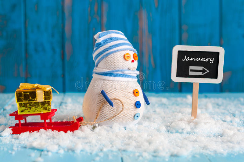 Uttrycka Januari som är skriftlig på den riktningstecken och snögubben fotografering för bildbyråer