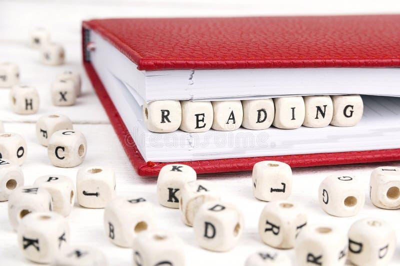 Uttrycka läs- skriftligt i träkvarter i röd anteckningsbok på vit w royaltyfri fotografi