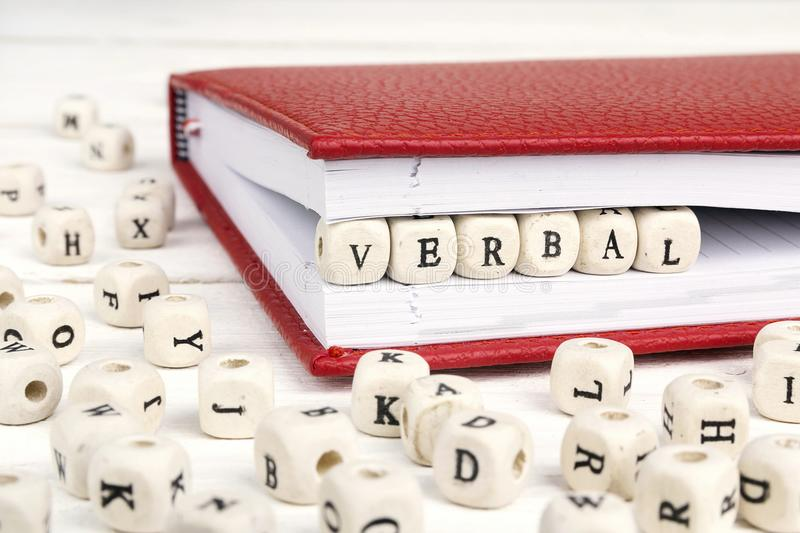 Uttrycka muntligt skriftligt i träkvarter i röd anteckningsbok på vit wo arkivbild