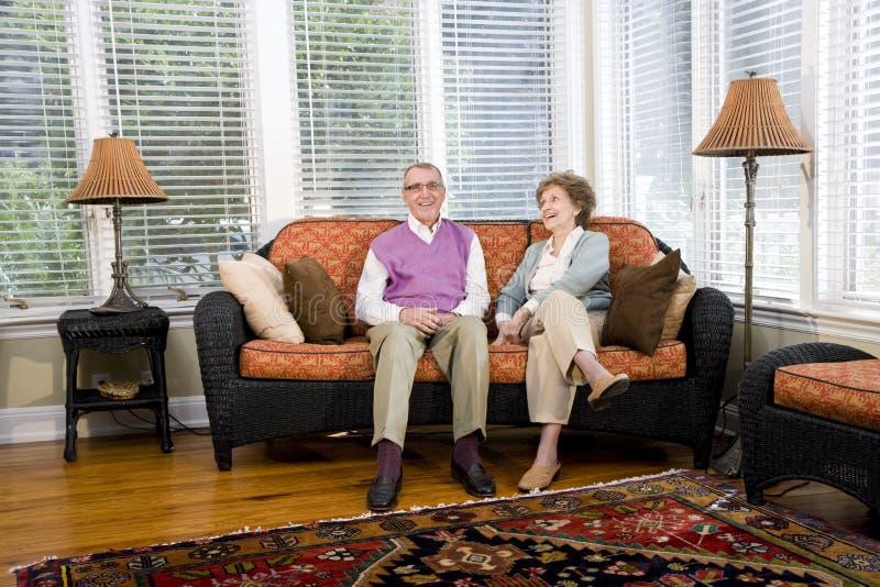 uttrycka sitting för lyckligt vardagsrum för par hög arkivbilder