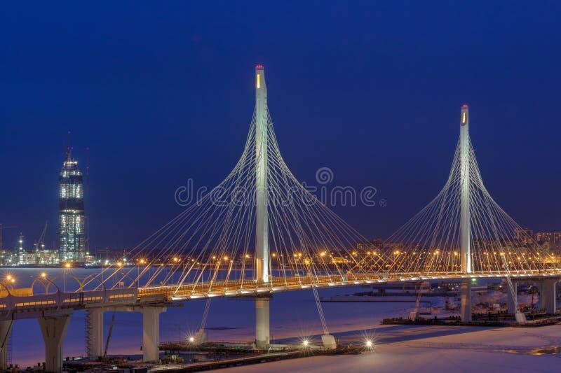 Uttryckliga vägar korsar den isbundna floden, guyed bro på nattligh royaltyfria foton