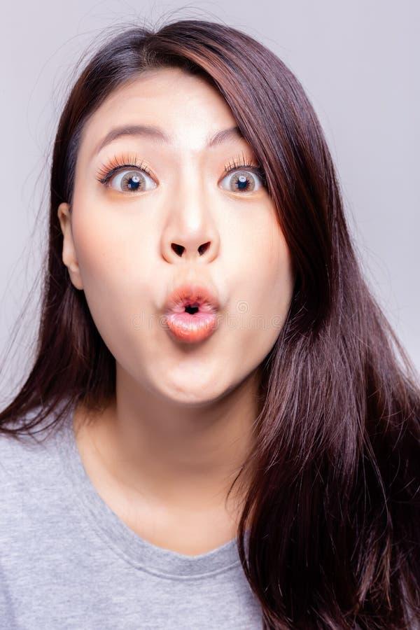 Uttrycksbegrepp Den härliga unga kvinnan som kysser eller gör, förkortar munnen Den asiatiska kvinnan är den skämtsamma kvinnan H royaltyfria bilder