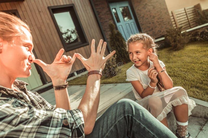 Uttrycksfull att bry sig fader som gör en gest aktivt, medan spela med ungen royaltyfri bild
