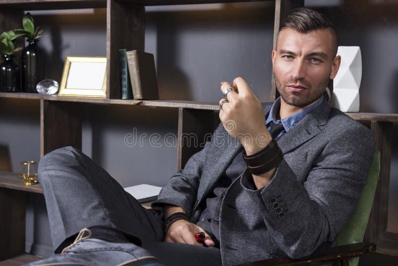 Uttrycksfull blick av en stilig man i en affärsdräkt, som sitter i en stol i en lyxig lägenhet med ett röka rör royaltyfri foto