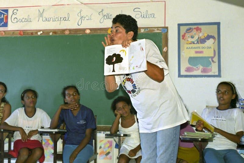 Uttrycksfull Braziliaan lärare som läser för flickor arkivbild