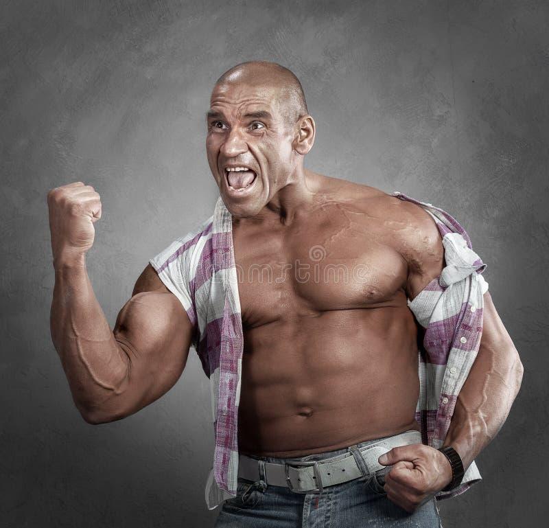 Uttrycksfull ilsken muskulös manvisninggest hans näve arkivbild