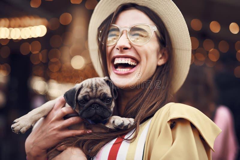 Uttrycksfull kvinna som rymmer den lilla valpen och att skratta royaltyfri bild