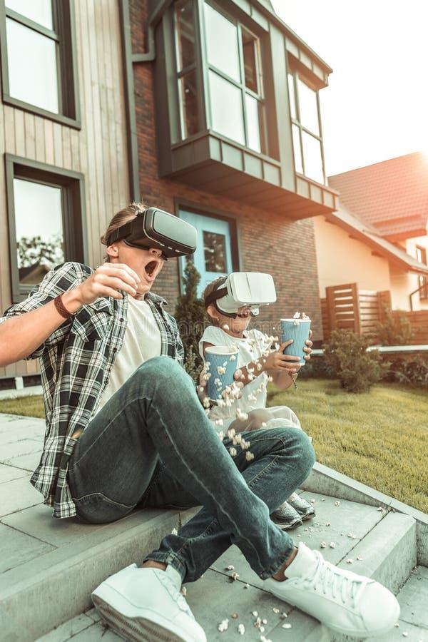 Uttrycksfull modern familj som sitter på trappan i VR-hjälmar royaltyfri fotografi