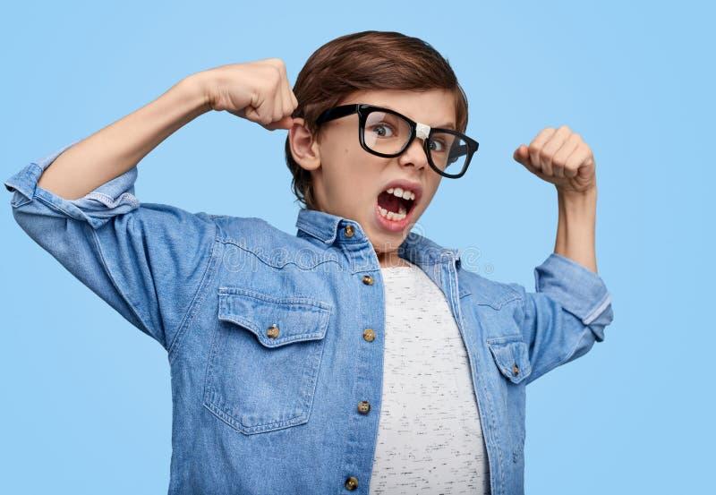Uttrycksfull nerdy pojke som visar biceps royaltyfri fotografi