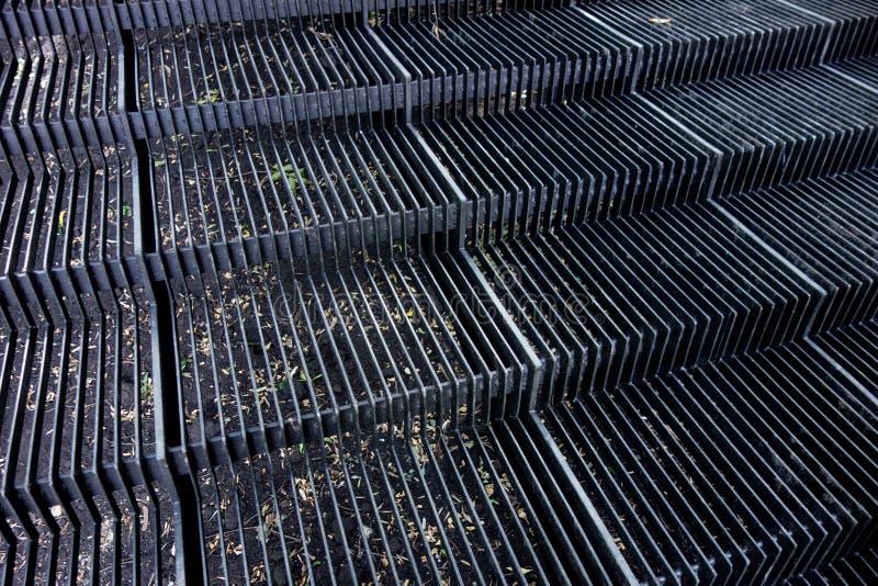 Utvändig metalltrapparam Moment från järnremmar och mellanrum Industriella strukturella linjer bakgrund Benägen sikt för perspekt arkivbild