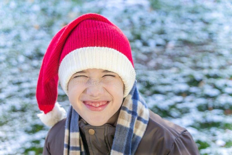 Utvändig pojke bära ett stuckit santa lock, skratta och scrunching arkivfoton