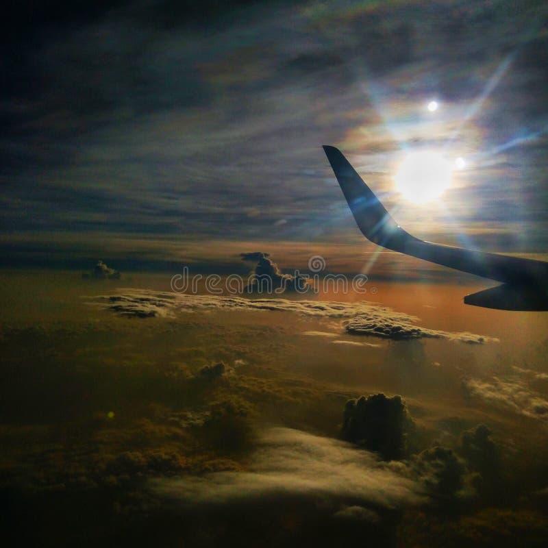 Utvändig sikt från flygplanet med den härliga solen & molnen royaltyfri fotografi