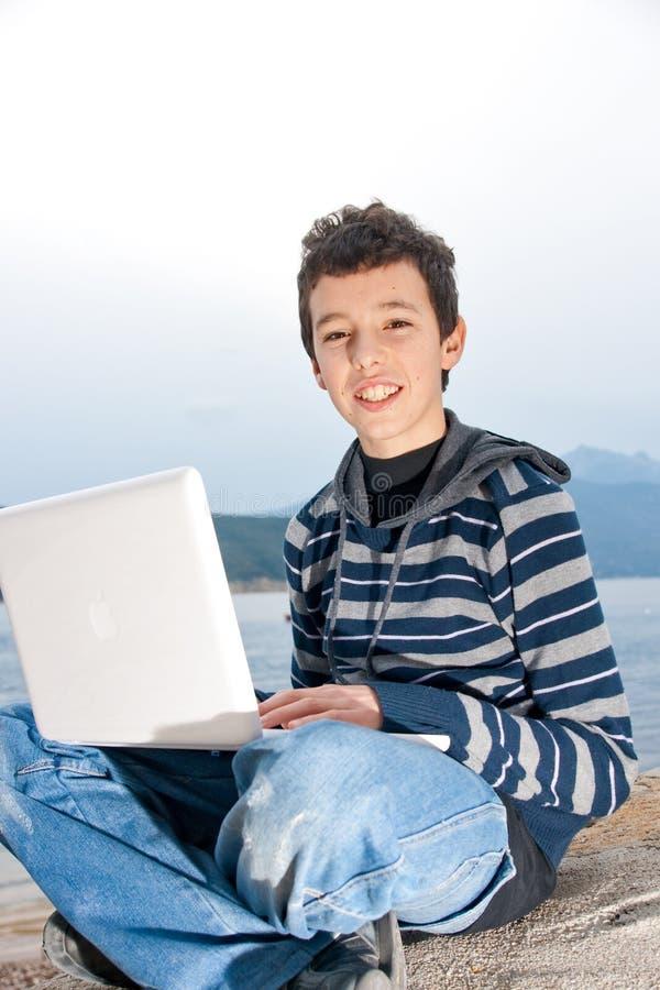 utvändigt användande barn för pojkebärbar dator fotografering för bildbyråer