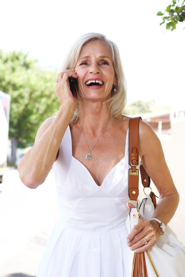 Utvändigt samtal för äldre kvinna på mobiltelefonen med handväskan arkivbild