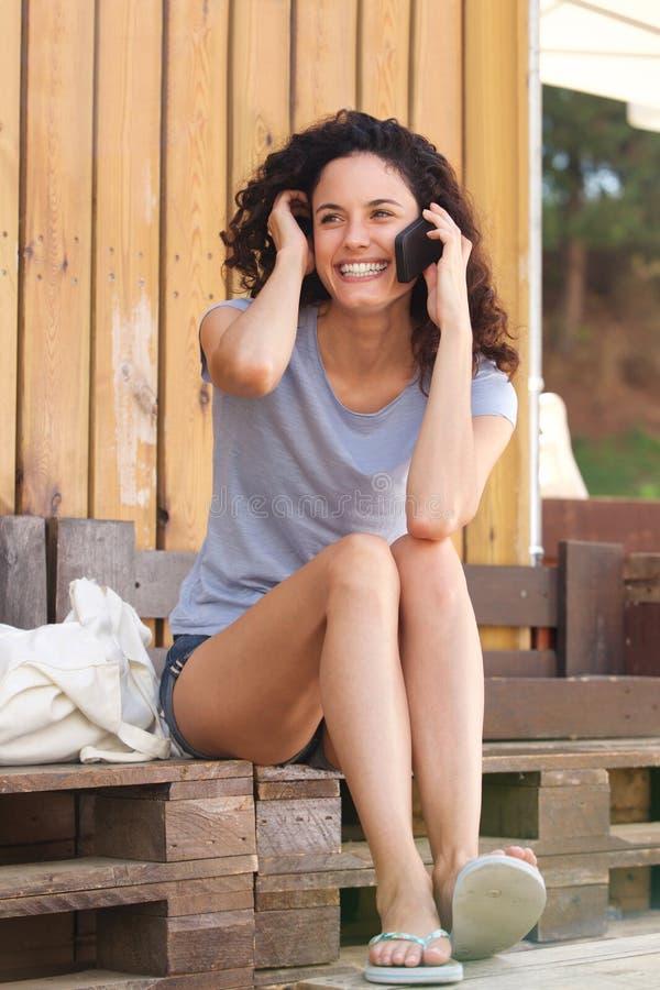 Utvändigt samtal för lyckligt sammanträde för ung kvinna med mobiltelefonen royaltyfri fotografi