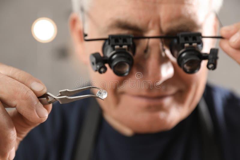 Utvärderande gemstone för manlig juvelerare i seminarium royaltyfri fotografi