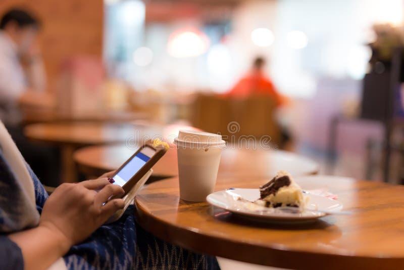 Utvald fokuskopp kaffe med kvinnan som använder cellhonen och eati royaltyfri bild