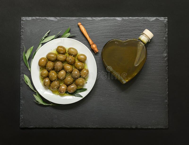 Utvalda oliv i en vit platta dekorerade med den naturliga olivträdfilialer och olivoljahjärtaflaskan arkivbilder
