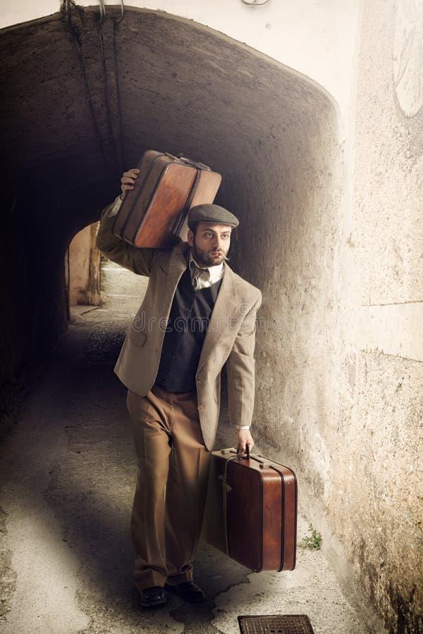 Utvandrareman med resväskorna i en liten stad arkivbild