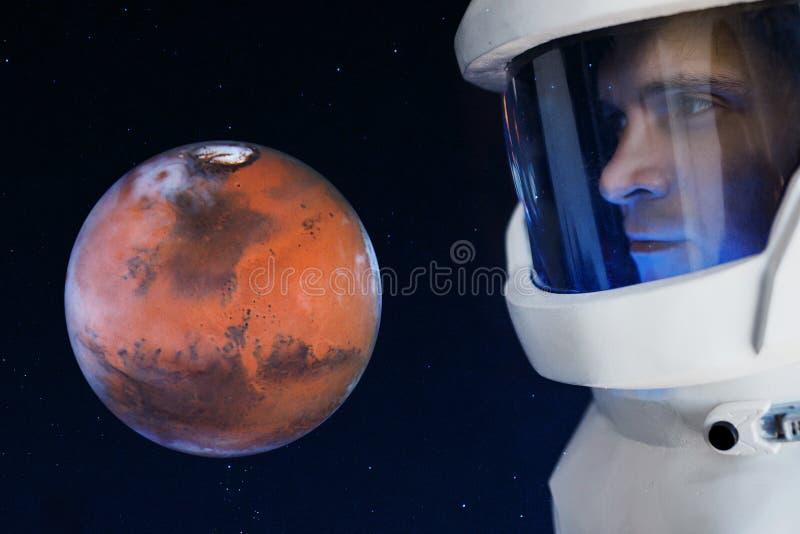 Utveckling av Mars, begrepp Astronautet som ser planeten, fördärvar Beståndsdelar av denna avbildar möblerat av NASA arkivbild