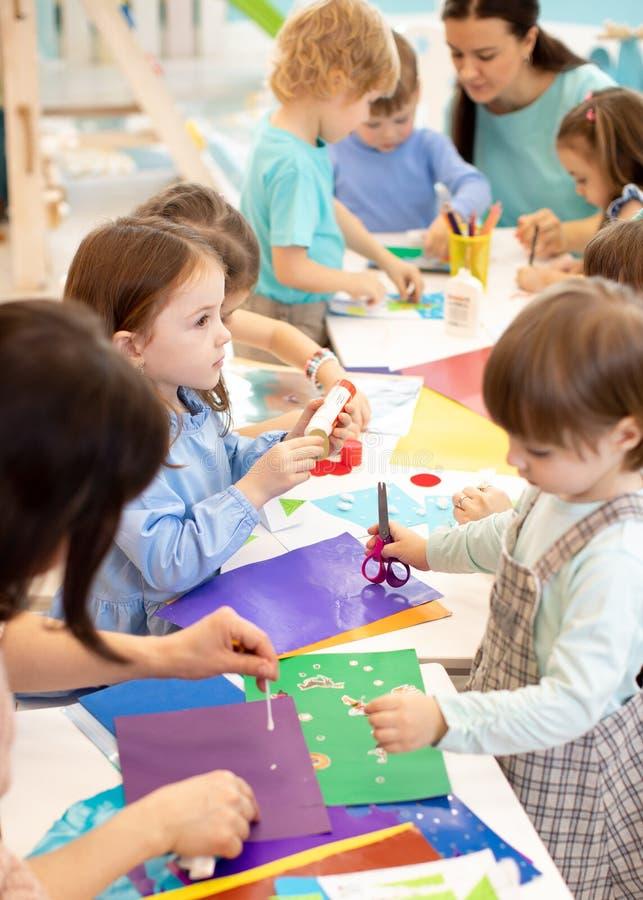 Utveckling som l?r barn i f?rtr?ning Projekt f?r barn` s i dagis Grupp av ungar och l?raren som klipper papper royaltyfri foto