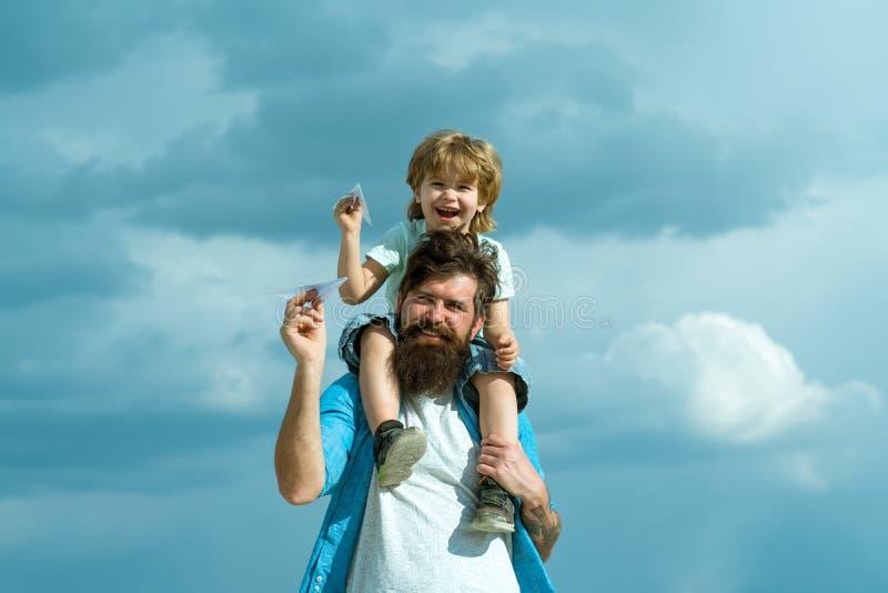 Utveckling tillbaka fader som ger parkrittsonen Fader och son som tillsammans bygger ett pappers- flygplan St?ende av lyckligt arkivfoton