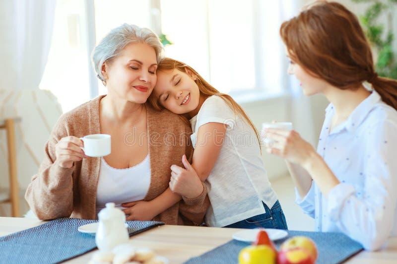 Utvecklingar för familj tre farmor, moder och barn som hemma kramar i kök royaltyfri fotografi