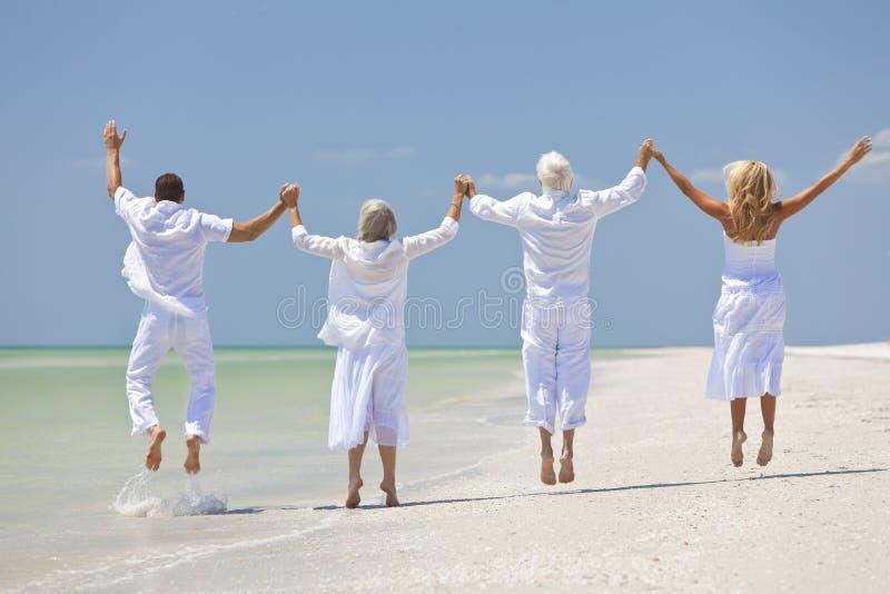 Utvecklingar för folkpensionärfamilj som hoppar på strand royaltyfri foto