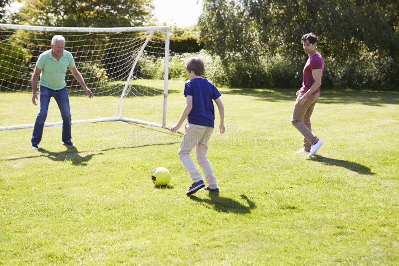 Utvecklingsfamilj för man som tre spelar fotboll tillsammans fotografering för bildbyråer