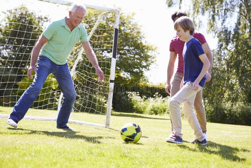 Utvecklingsfamilj för man som tre spelar fotboll tillsammans royaltyfria foton