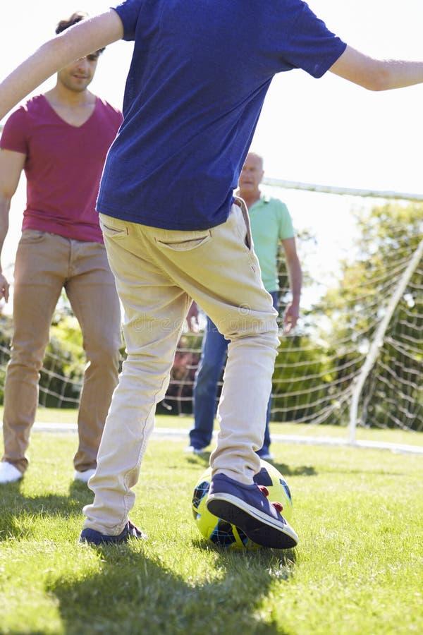 Utvecklingsfamilj för man som tre spelar fotboll tillsammans arkivbilder