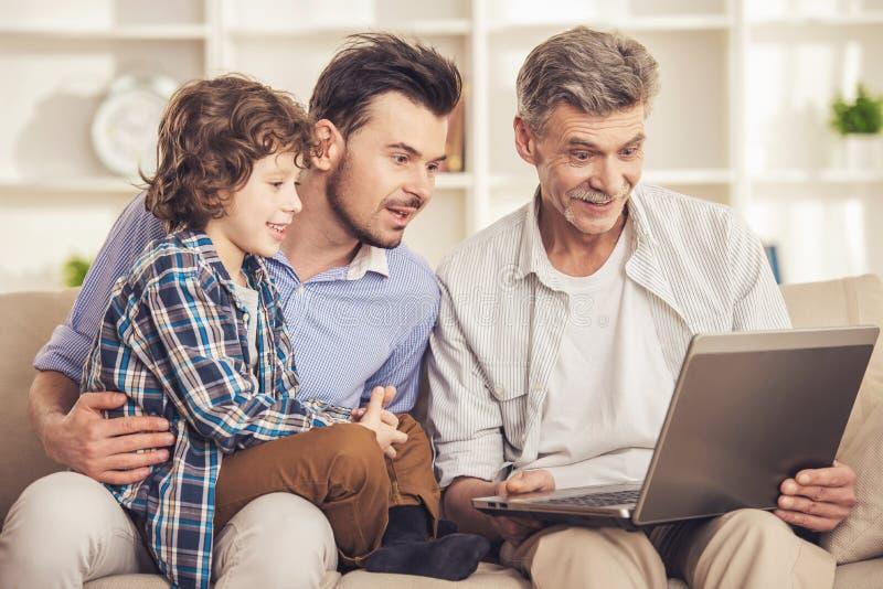 Utvecklingsstående Farfar-, fader- och sonsammanträde och användabärbar dator på soffan arkivbild