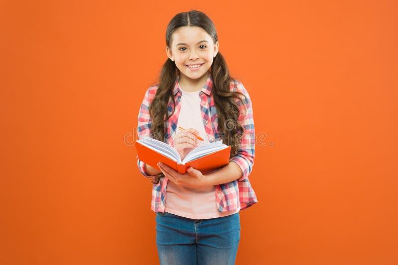 Utvidga din mening, l?s en bok Småbarnläsebok på orange bakgrund Liten flicka som rymmer textboken intressera royaltyfria bilder