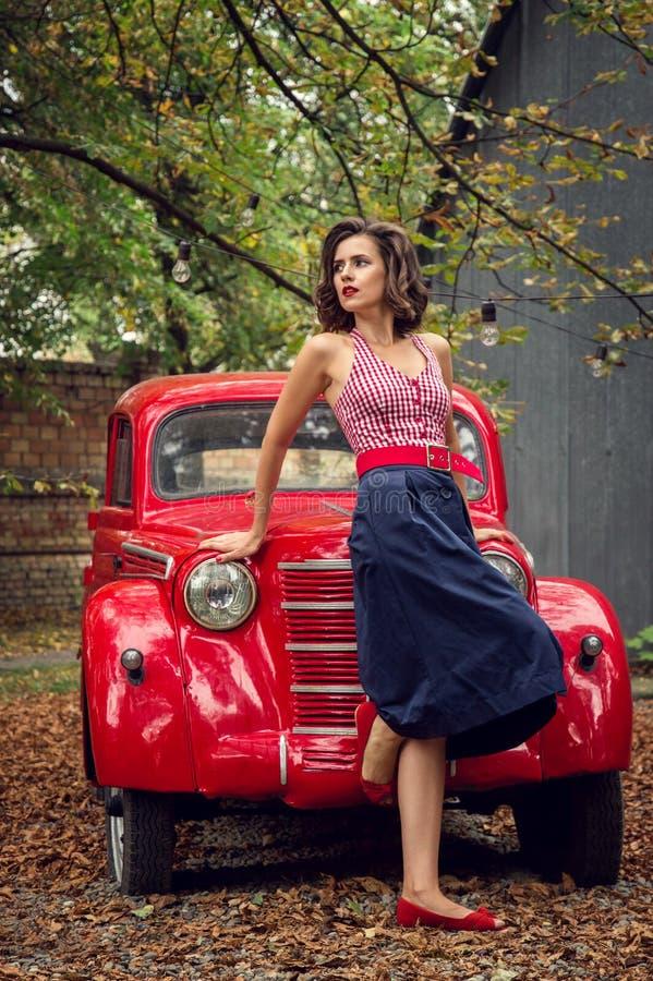 Utvikningsflicka som poserar på en retro bilbakgrund för röd ryss En skämtsam intresserad blick gjutas åt sidan royaltyfri bild