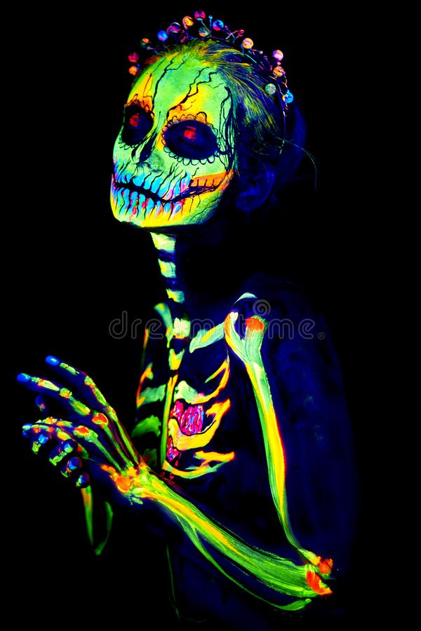 UV body art painting of helloween female skeleton. Día de los Muertos stock photography